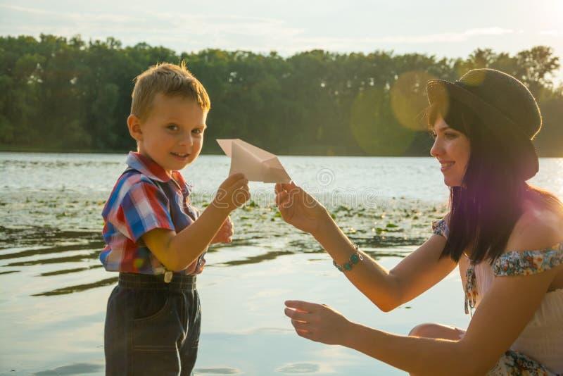 Niño pequeño que juega con el aeroplano de papel con su madre al aire libre fotografía de archivo