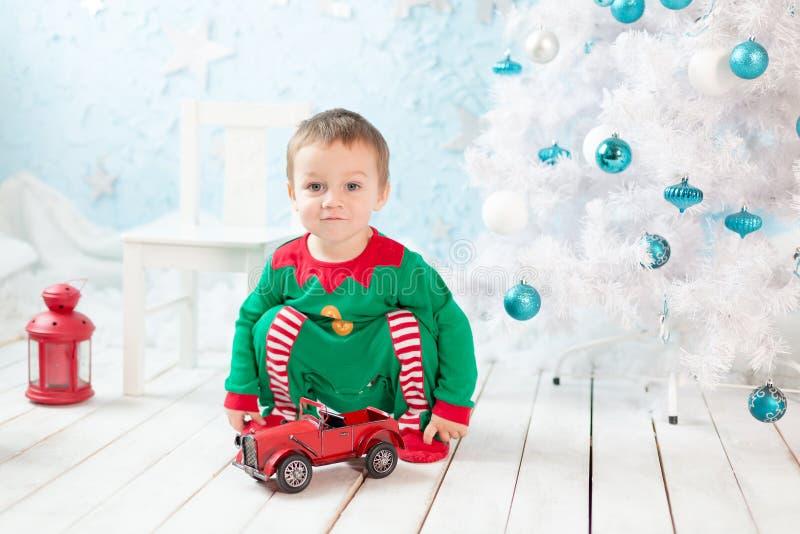 Niño pequeño que juega con el pequeño coche cerca de árbol de Navidad imagen de archivo