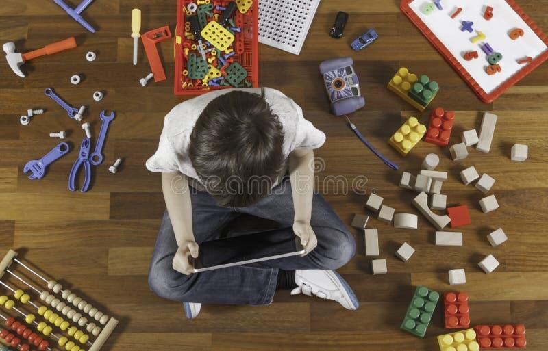 Niño pequeño que juega con la tableta Porción de juguetes alrededor de él en el piso de madera Visión superior fotografía de archivo