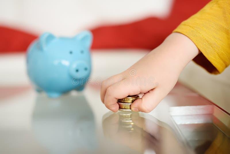 Niño pequeño que juega con las monedas y los sueños de lo que él puede comprar Educación de niños en la instrucción financiera foto de archivo