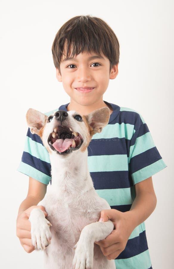 Niño pequeño que juega con su enchufe Russel del perro del amigo foto de archivo libre de regalías