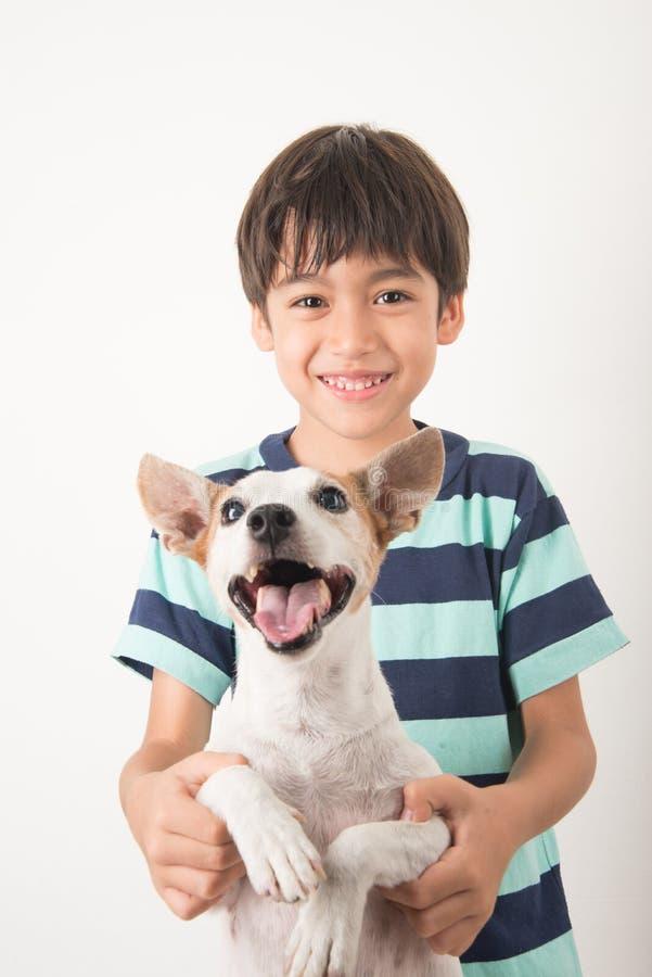 Niño pequeño que juega con su enchufe Russel del perro del amigo en blanco foto de archivo