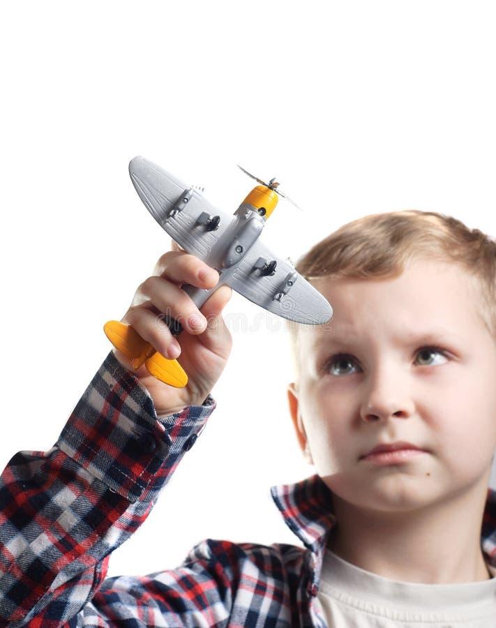 Niño pequeño que juega con un aeroplano modelo que finge ser un piloto fotos de archivo libres de regalías