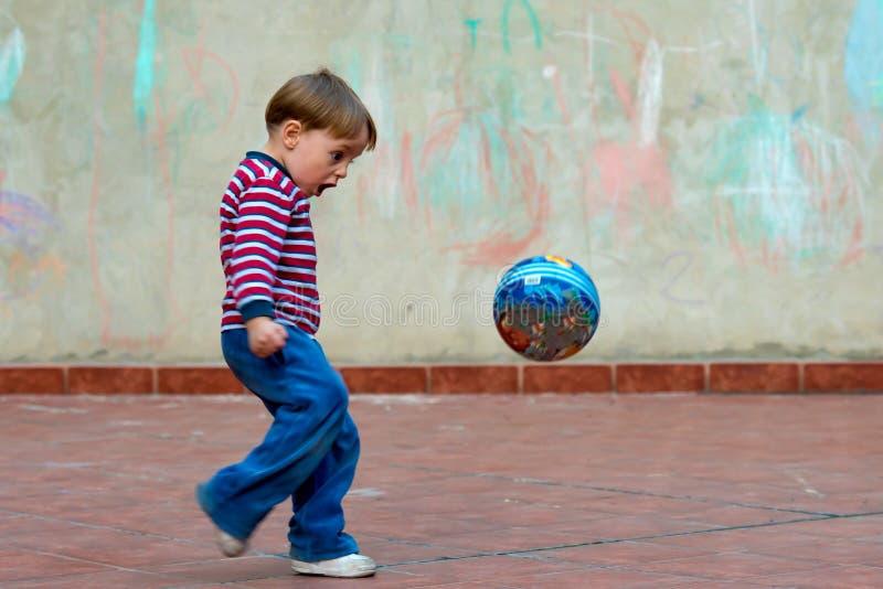 Niño pequeño que juega con una bola foto de archivo libre de regalías