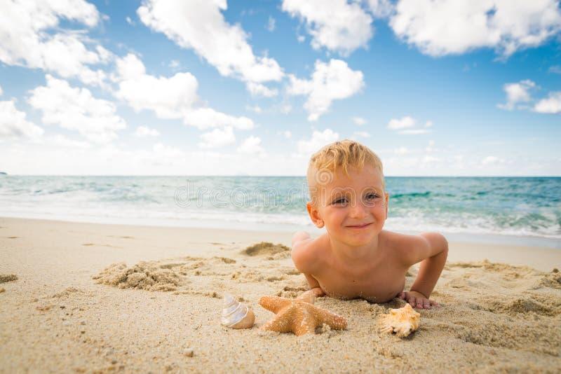 Niño pequeño que juega con una estrella de mar en la playa foto de archivo libre de regalías