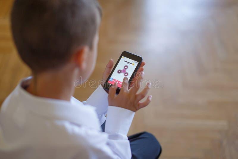 Niño pequeño que juega en hilandero del smartphone imagen de archivo libre de regalías