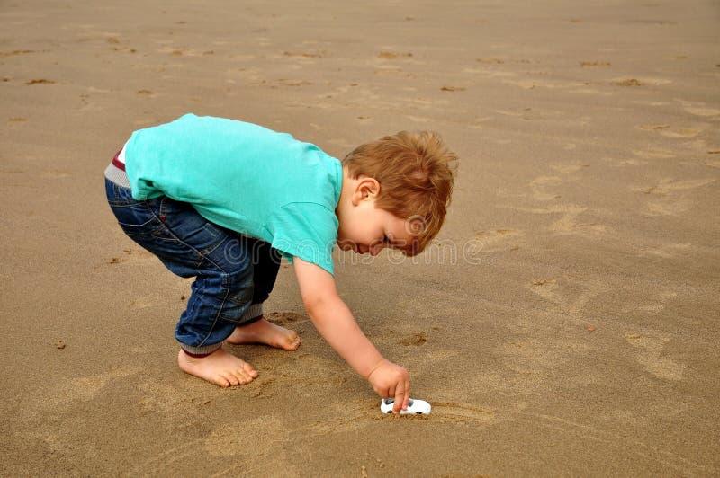 Niño pequeño que juega en la playa foto de archivo