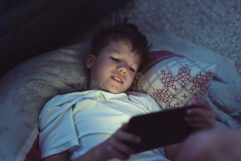 Niño pequeño que juega en la tableta en la noche en dormitorio foto de archivo libre de regalías