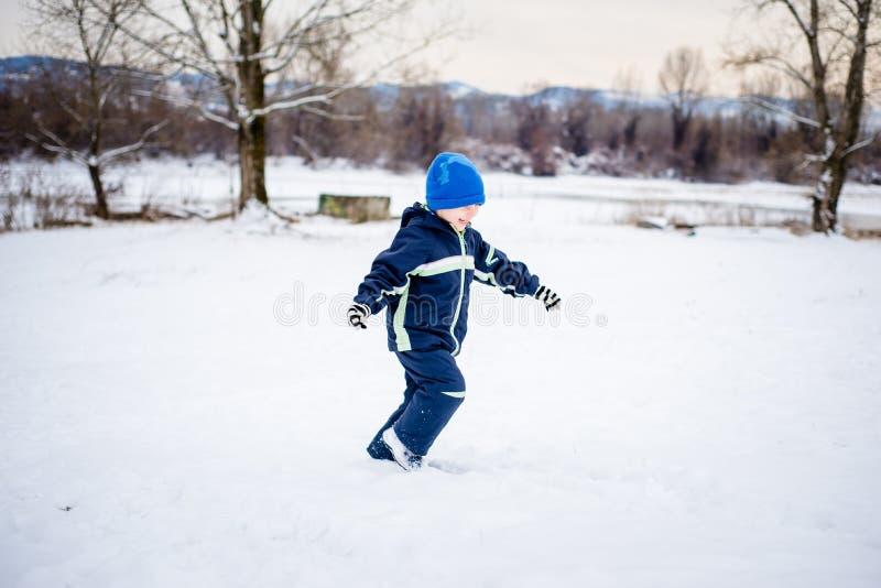 Niño pequeño que juega en nieve fotografía de archivo libre de regalías