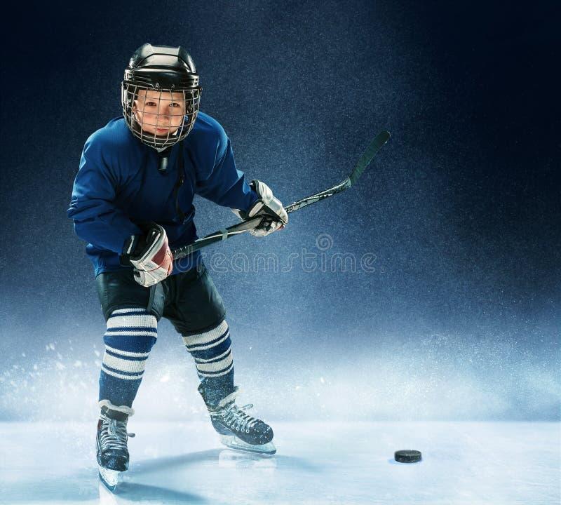 Niño pequeño que juega a hockey sobre hielo fotos de archivo