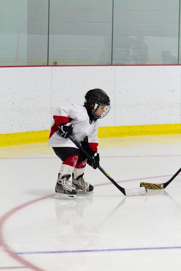Niño pequeño que juega a hockey sobre hielo fotografía de archivo