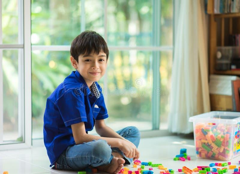 Niño pequeño que juega la casa interior del bloque foto de archivo