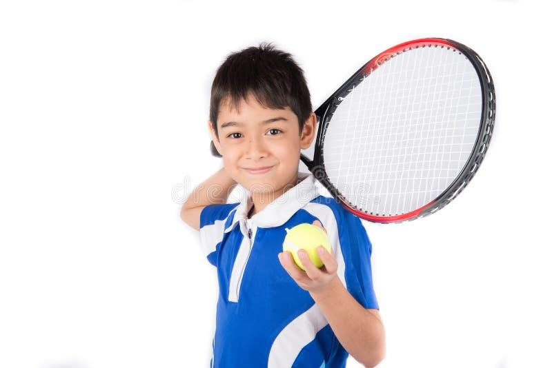 Niño pequeño que juega la estafa de tenis y la pelota de tenis a disposición imagenes de archivo
