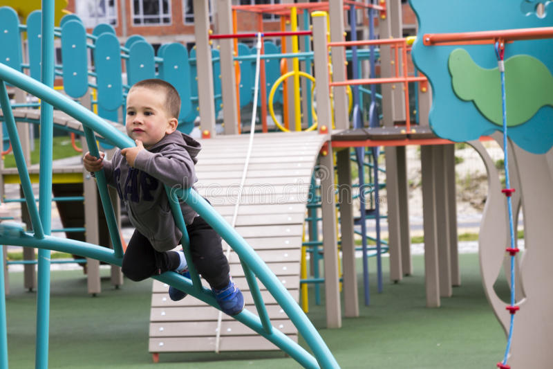 Niño pequeño que juega la oscilación en el patio en parque imagen de archivo