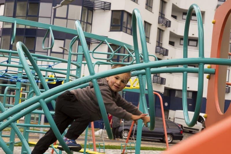 Niño pequeño que juega la oscilación en el patio en parque imágenes de archivo libres de regalías