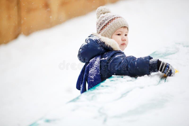 Niño pequeño que juega solamente con el juguete en la nieve, cierre para arriba Afuera, invierno imagenes de archivo