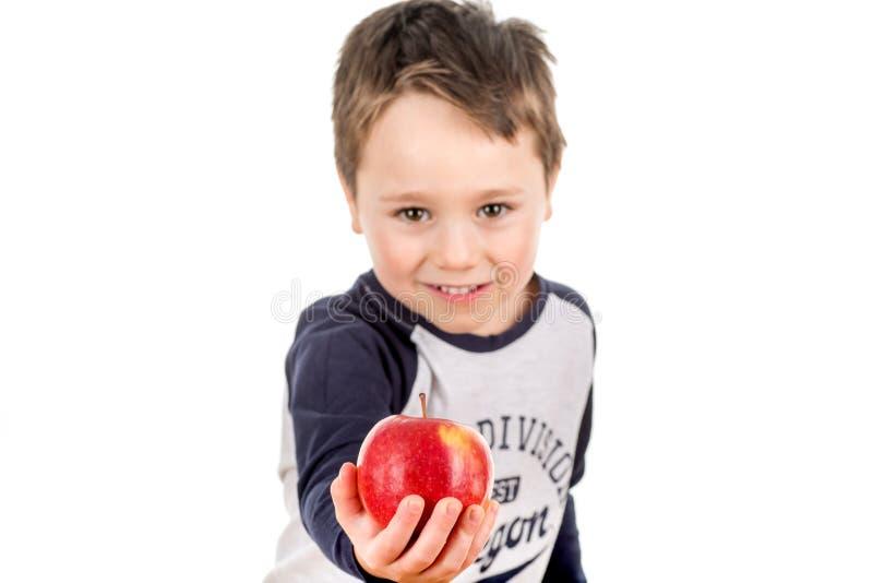 Niño pequeño que lleva a cabo la distribución de una manzana Coma esto imágenes de archivo libres de regalías