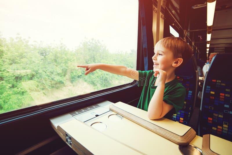 Niño pequeño que mira hacia fuera la ventana del tren Niño que señala afuera de ventana del tren Vacaciones de familia y el viaja fotos de archivo libres de regalías