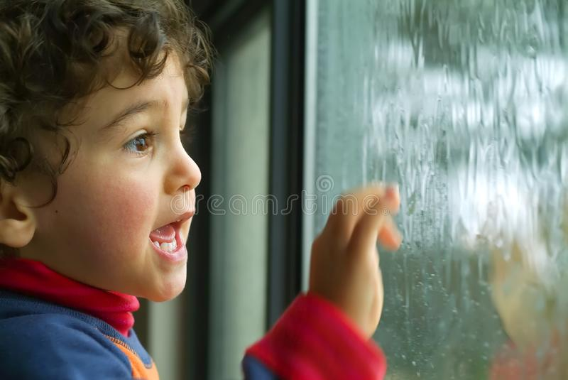 Niño pequeño que mira la lluvia foto de archivo