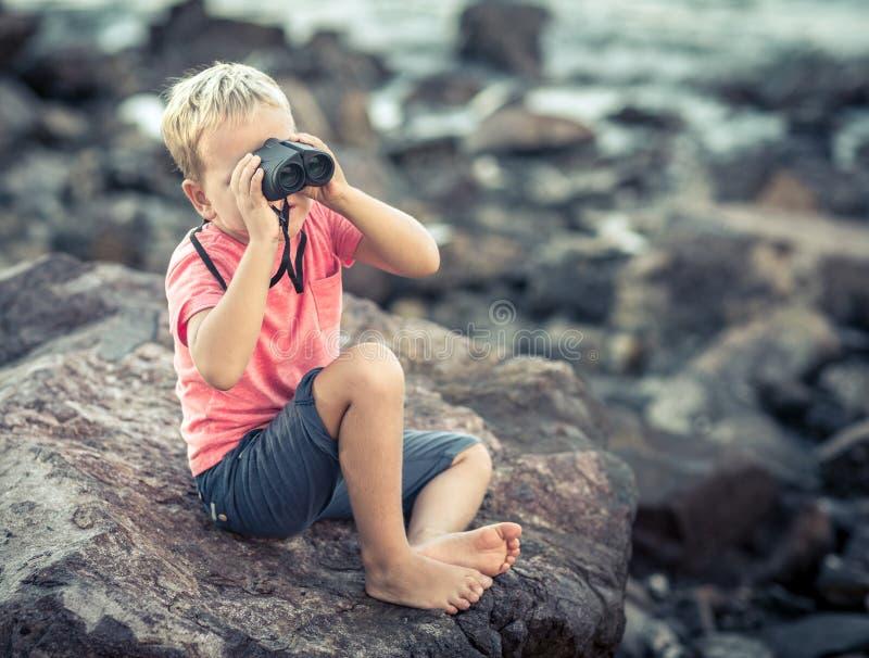 Niño pequeño que mira lejos con los prismáticos imágenes de archivo libres de regalías