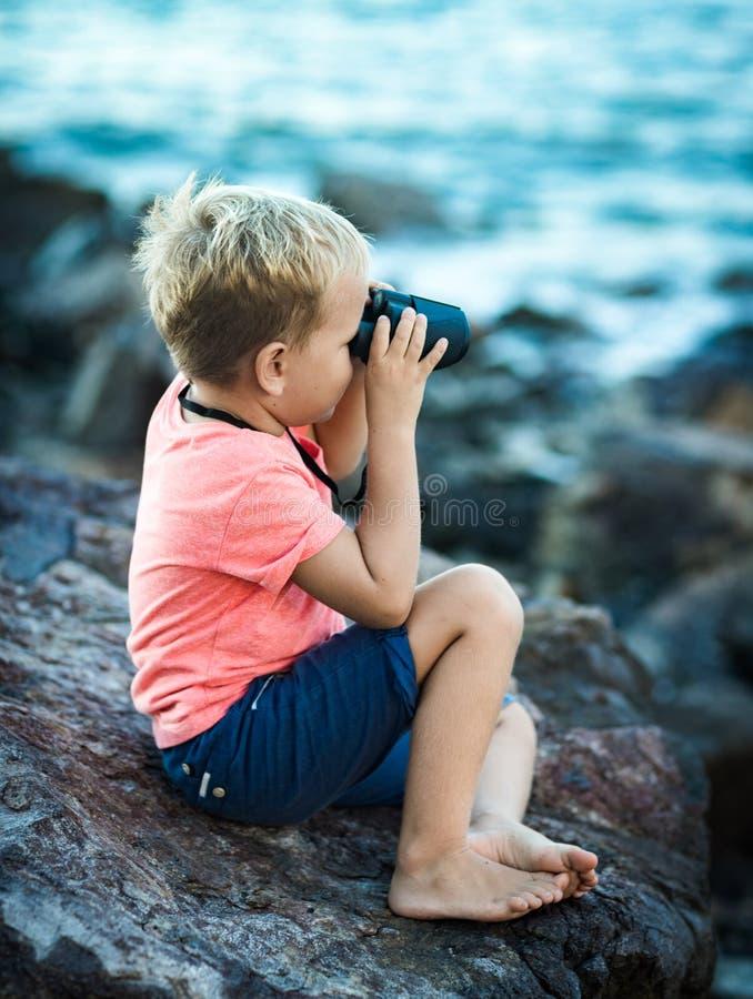 Niño pequeño que mira lejos con los prismáticos foto de archivo