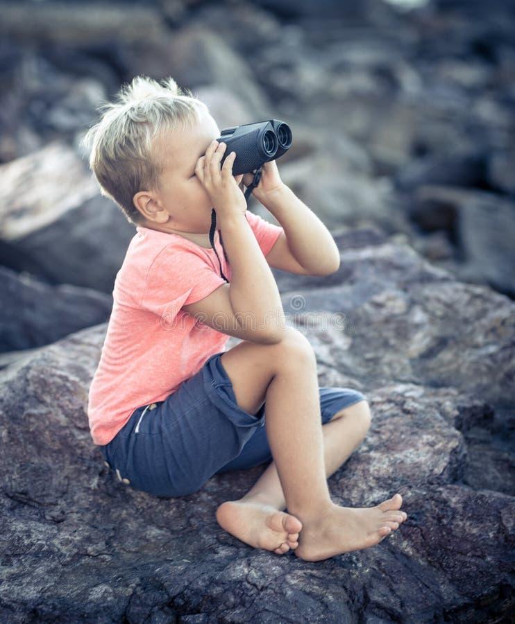 Niño pequeño que mira lejos con los prismáticos fotos de archivo