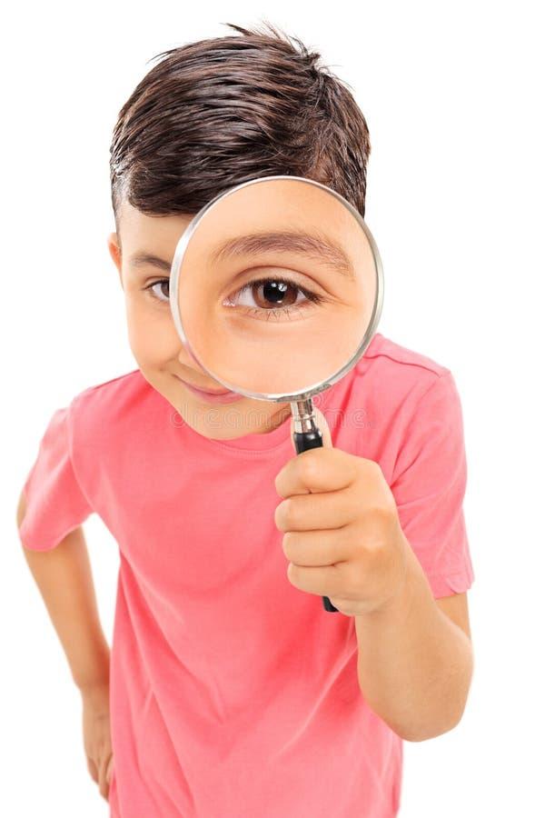 Niño pequeño que mira a través de una lupa imagenes de archivo