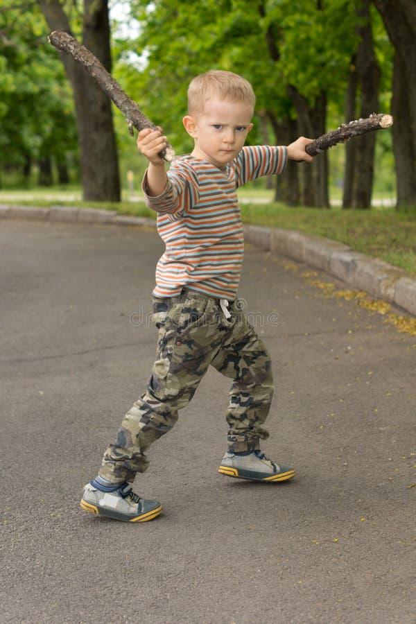 Niño pequeño que muestra apagado sus habilidades que luchan del palillo imagen de archivo