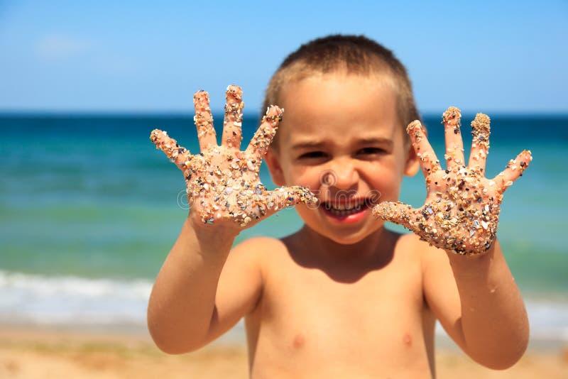 Niño pequeño que muestra las manos arenosas imagenes de archivo