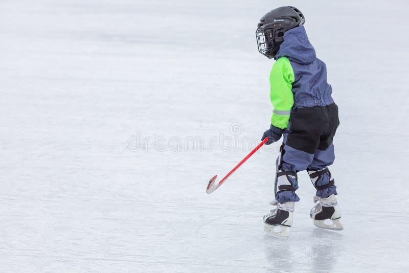 Niño pequeño que patina y que juega a hockey foto de archivo