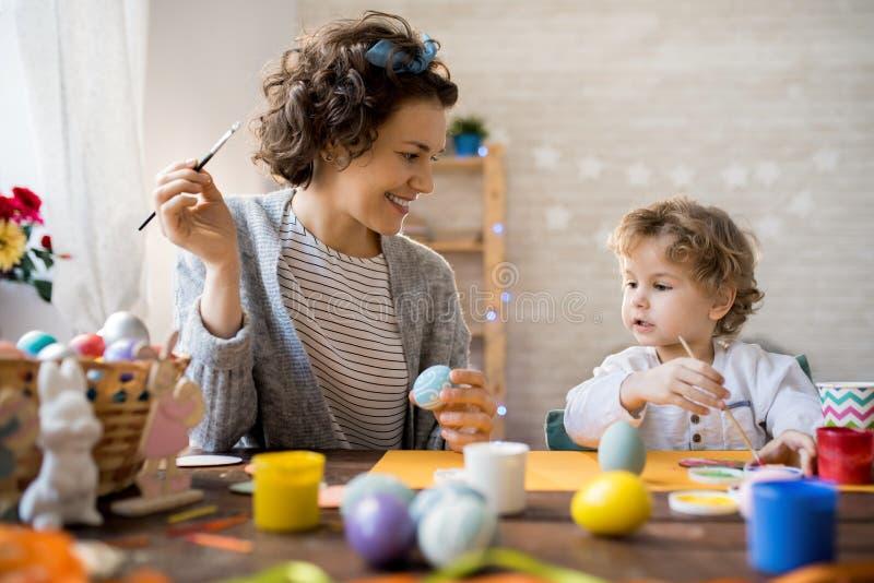 Niño pequeño que pinta los huevos de Pascua imagen de archivo