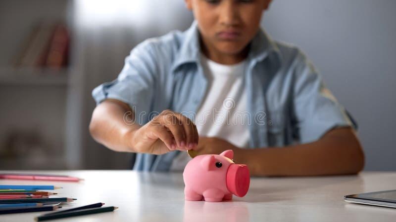 Niño pequeño que pone el dinero suelto en la hucha, aumentando los fondos para el juguete deseado imágenes de archivo libres de regalías