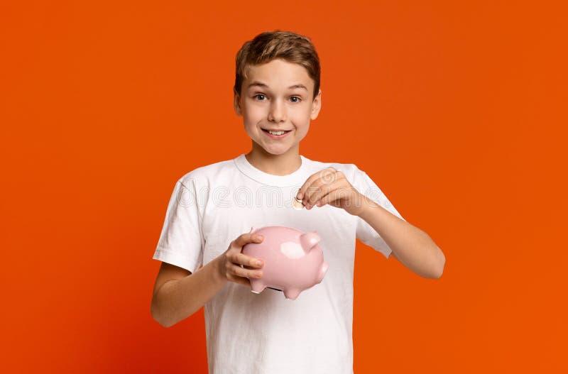 Niño pequeño que pone el dinero suelto en la hucha fotografía de archivo libre de regalías