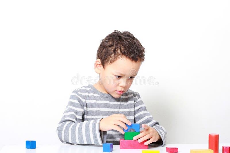 Niño pequeño que prueba su creatividad construyendo torres con las unidades de creación del juguete imagenes de archivo