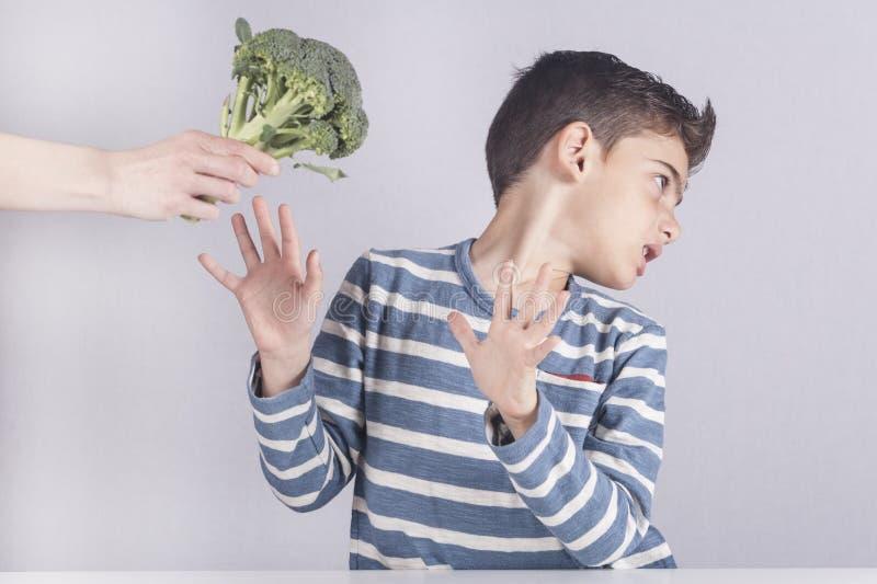 Niño pequeño que rechaza comer sus verduras fotografía de archivo