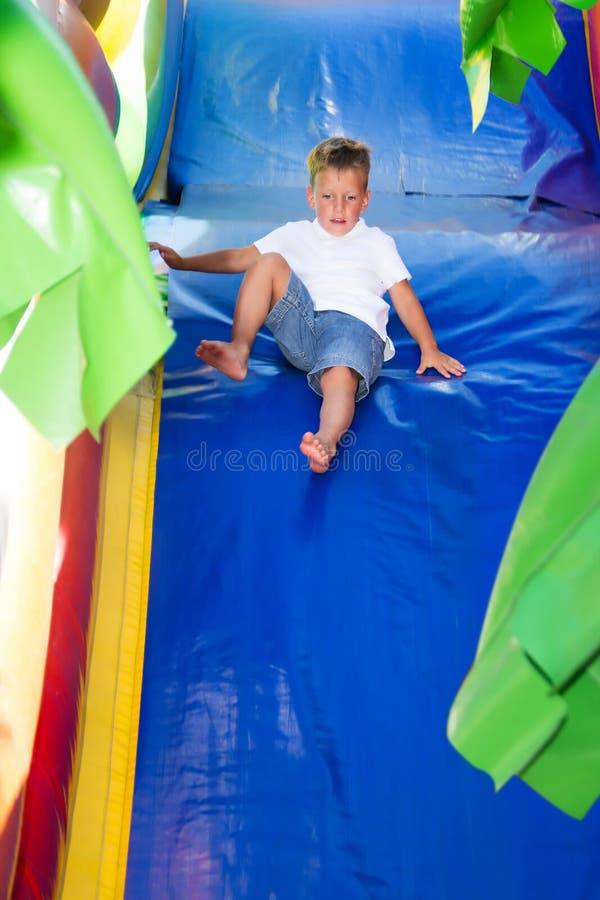 Niño pequeño que resbala en la colina inflable imagen de archivo libre de regalías