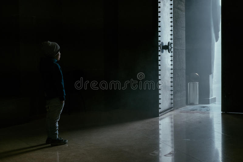 Niño pequeño que se coloca cerca de puerta abierta fotos de archivo libres de regalías