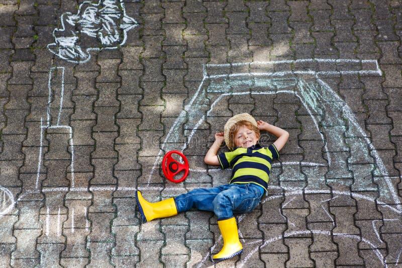 Niño pequeño que se divierte con el dibujo de la imagen del tractor con tiza foto de archivo libre de regalías