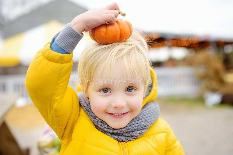 Niño pequeño que se divierte en un viaje de una granja de la calabaza en el otoño Niño que se sienta en la calabaza gigante imágenes de archivo libres de regalías