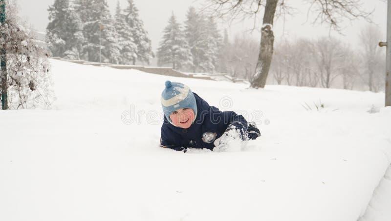 Niño pequeño que se divierte que forcejea en la nieve en parque del invierno imágenes de archivo libres de regalías