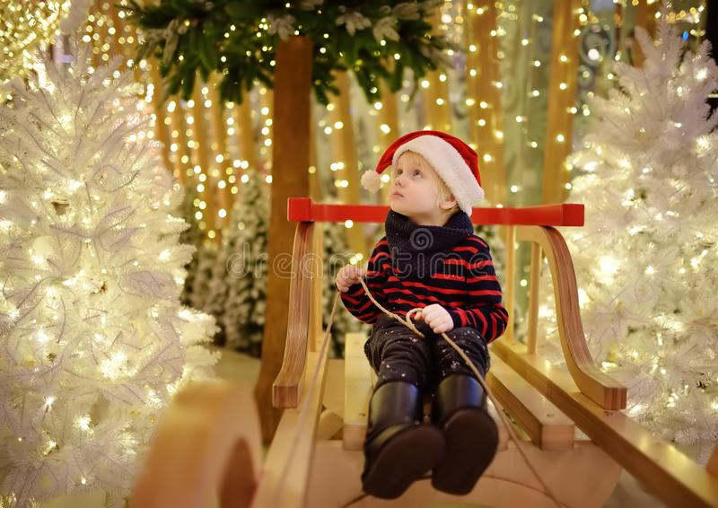 Niño pequeño que se divierte y que hace la foto en la instalación de la Navidad con las luces en fondo Compras de la Navidad de l imagenes de archivo