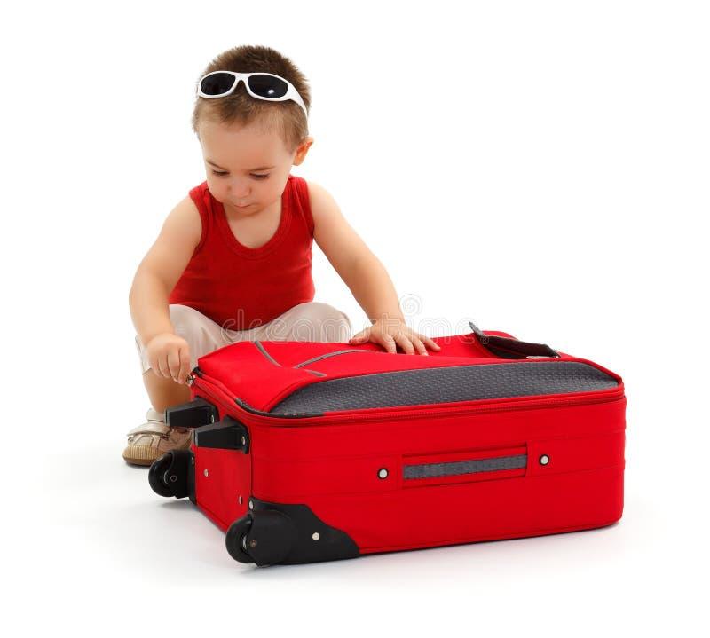 Niño pequeño que se prepara para el viaje, relampagando la maleta fotos de archivo