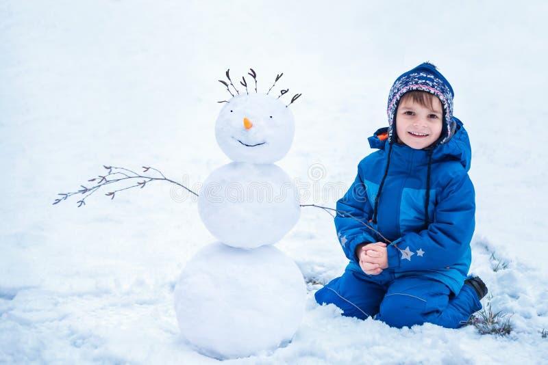 Niño pequeño que se sienta cerca del muñeco de nieve sonriente imagenes de archivo