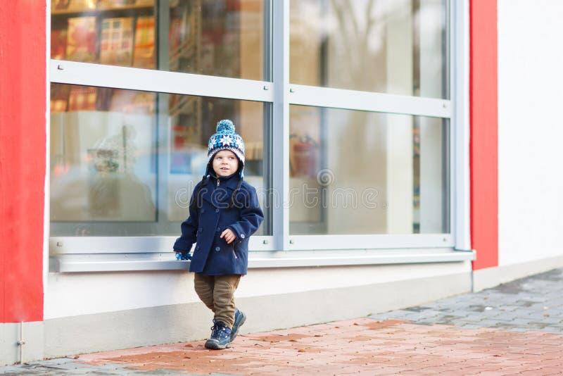 Niño pequeño que se sienta delante de ventana grande en la ciudad, al aire libre, imagenes de archivo