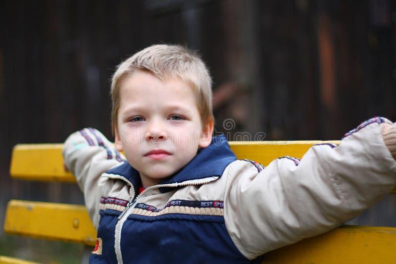 Niño pequeño que se sienta en el banco fotos de archivo libres de regalías