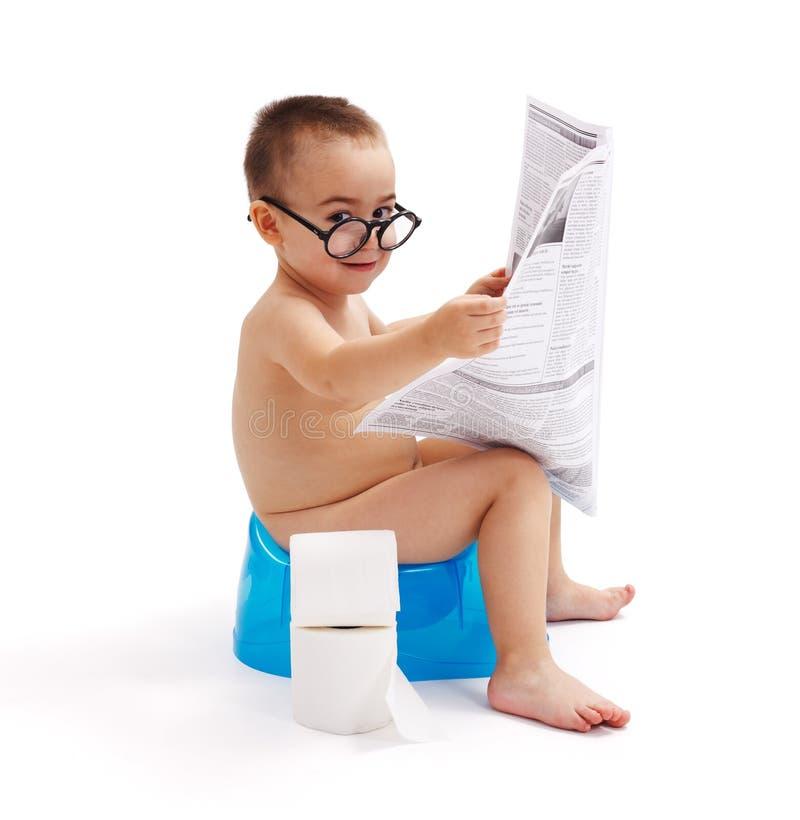 Niño pequeño que se sienta en el periódico insignificante y de lectura fotografía de archivo libre de regalías