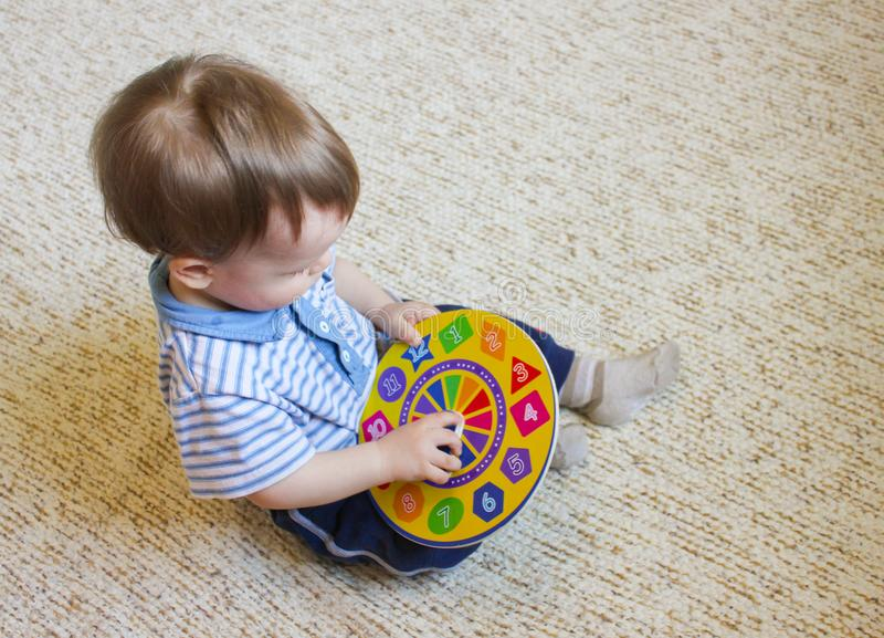 Niño pequeño que se sienta en el piso y los juegos con un reloj del juguete E foto de archivo