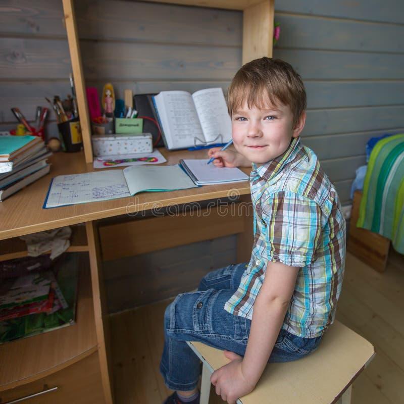 Niño pequeño que se sienta en la tabla que hace la preparación de la escuela Educación foto de archivo libre de regalías
