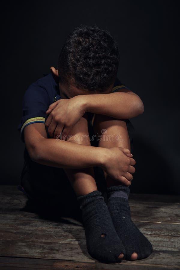 Niño pequeño que se sienta en piso en oscuridad fotos de archivo