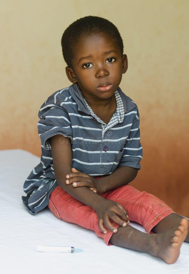 Niño pequeño que se sienta en un hospital que espera para conseguir una inyección imagen de archivo libre de regalías